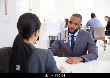 Businessman and woman sitting at desk in an open plan office - Stock Photo