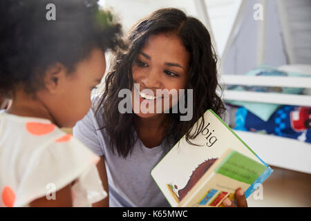 Mother And Baby Daughter Reading Book In Playroom Together - Stock Photo