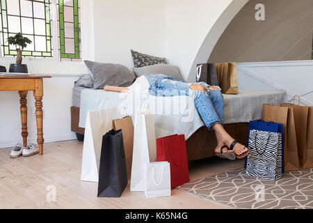 Woman Back From Shopping Trip Surrounded By Bags Lies On Bed - Stock Photo