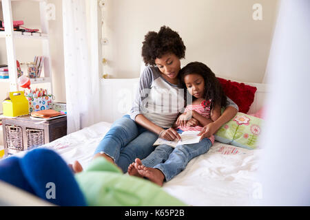 Mother And Daughter Siting On Bed Reading Book Together - Stock Photo