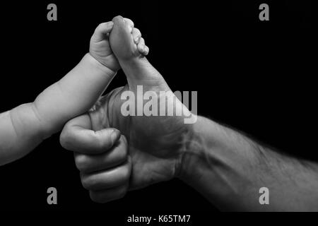 Small and big hand, baby holds father's thumb - Stock Photo
