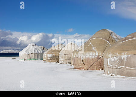 Yurts in traditional Kyrgyz yurt camp in the snow along Song Kul / Song Kol lake in the Tian Shan Mountains, Naryn - Stock Photo