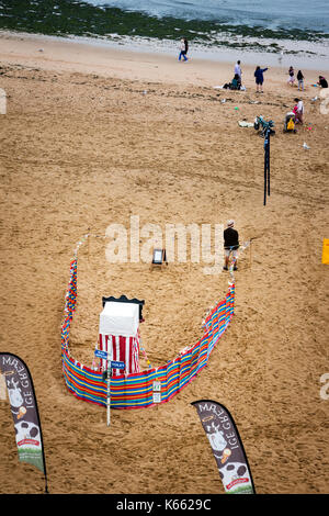 England, Broadstairs. Aerial view of lone Punch and Judy man standing by show entrance on almost deserted beach - Stock Photo
