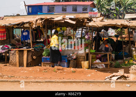 Fruit and vegetable market stalls with people sitting and browsing, Kenya - Stock Photo