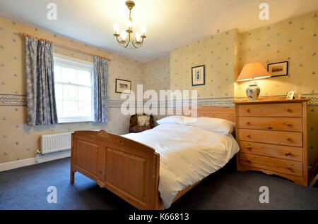 Guest bedroom in country cottage with pine furniture - Stock Photo