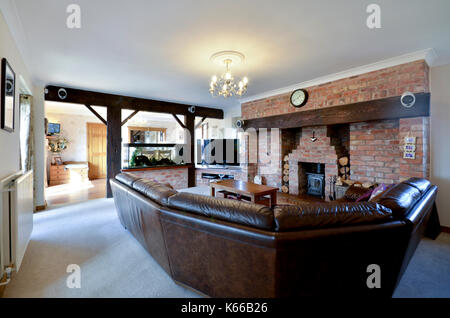 sitting room with exposed beams and large brick fireplace - Stock Photo