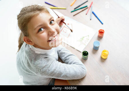 Happy smiling schoolgirl is drawing. Photo of a cute little girl doing homework. Education concept - Stock Photo