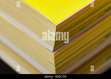 thickness of old versions of yellow pages classified telephone directory paper edition uk - Stock Photo