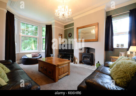 Lounge in family home with wood burning stove - Stock Photo