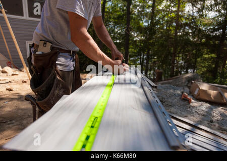 A construction worker marking vinyl siding using a pencil and a tape measure in Ontario, Canada. - Stock Photo