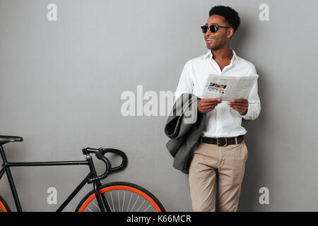Smiling stylish afro american man in sunglasses holding newspaper while standing near a bicycle isolated over gray - Stock Photo