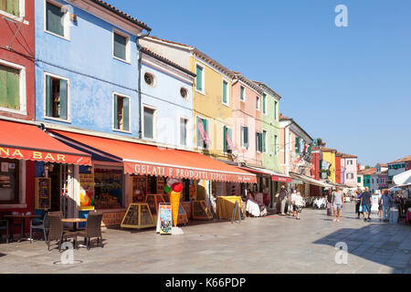 Tourists shopping at colorful stores and restaurants in Via Baldasarre Galuppi, Burano, Venice, Italy, a popular - Stock Photo