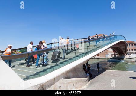 Tourists crossing the Calatrava Bridge or Ponte della Costituzione, Venice, Italy lugging their siutcases accompanied - Stock Photo