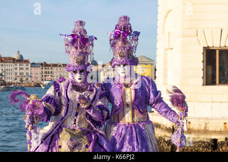 2017 Venice Carnival, Italy. Two women in colorful purple classical costumes posing at San Giorgio maggiore at sunset - Stock Photo