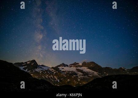 The Milky Way stars are rising behind Piz Cambrena and Piz Bernina at night - Stock Photo