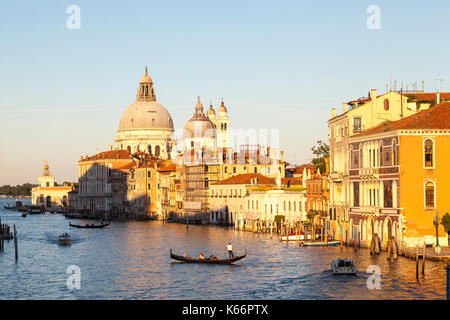 Sunset on the Grand Canal and Basilica Santa Maria della Salute, Venice, Italy with  a gondola and boats on the - Stock Photo