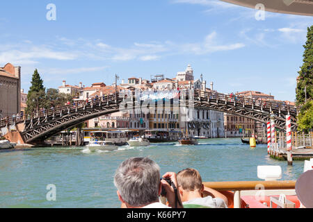 Tourists on a vaporetto travelling up the Grand Canal, Venice, Italy from a first person point of view onboard looking - Stock Photo