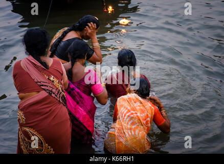 VARANASI, INDIA - CIRCA NOVEMBER 2016: Women worshiping and bathing in the Ganges river. Varanasi is the spiritual - Stock Photo