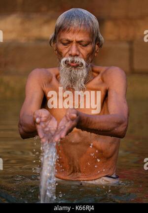 VARANASI, INDIA - CIRCA NOVEMBER 2016: Man worshiping in the Ganges river in Varanasi. Varanasi is the spiritual - Stock Photo