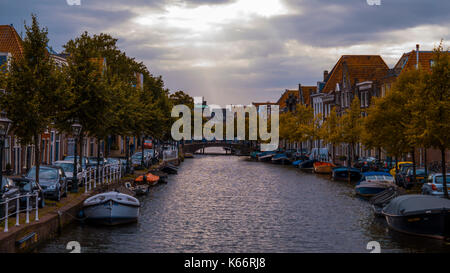 Water canals in Leiden, The Netherlands with boats, trees, old dutch houses with traditional dutch roofs and cars - Stock Photo