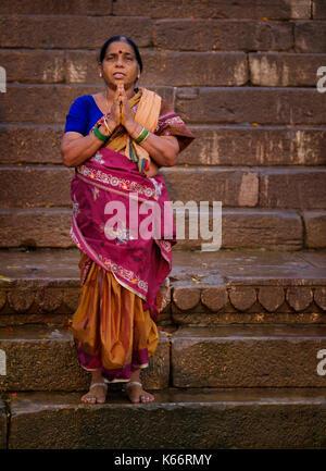 VARANASI, INDIA - CIRCA NOVEMBER 2016: Hindu woman worshiping in Varanasi. Varanasi is the spiritual capital of - Stock Photo