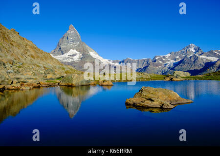 The East Face of the Matterhorn, Monte Cervino, mirroring in the Lake Riffelsee at sunrise - Stock Photo