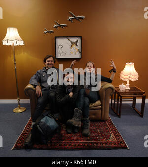 STANDALONE PHOTO Visitors sat on an installation by artist Banksy, entitled Civilian Drone Strike, on display at - Stock Photo