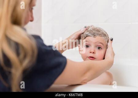 Caucasian mother washing hair of girl in bathtub - Stock Photo