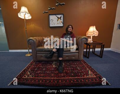 STANDALONE PHOTO A visitor sat on an installation by artist Banksy, entitled Civilian Drone Strike, on display at - Stock Photo