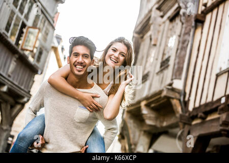 Man carrying woman piggyback in city - Stock Photo