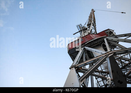 An old harbor crane viewed from down below against the blue sky - Stock Photo