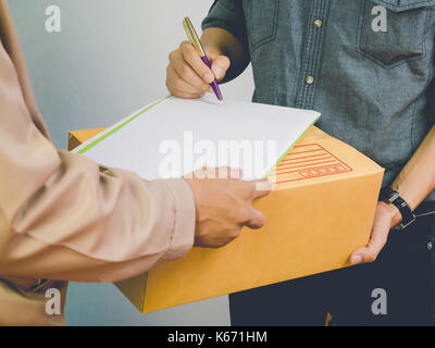 Man accepting a delivery of cardboard boxes from deliveryman - Stock Photo