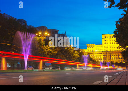 Liberty Boulevard at dusk with illuminated fountains looking toward the Palace of Parliament, the most loved and - Stock Photo