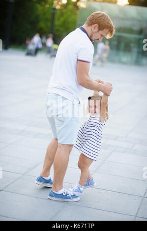 Young dad is playing with a charming little daughter. The man is holding the baby by the handles.. The child rejoices. - Stock Photo