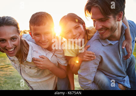 Young couple piggybacking their young children outdoors - Stock Photo