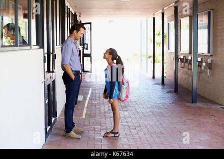 School teacher talking with schoolgirl outside classroom - Stock Photo