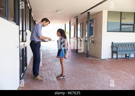 School teacher showing book to schoolgirl outside classroom - Stock Photo