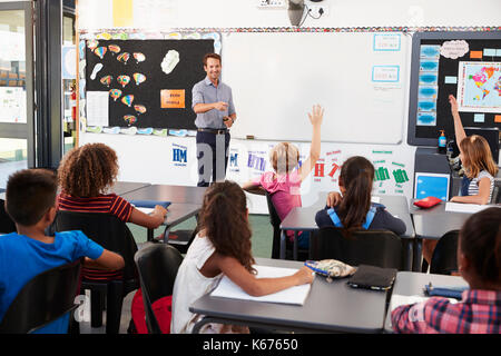 Teacher at front of class in an elementary school lesson - Stock Photo