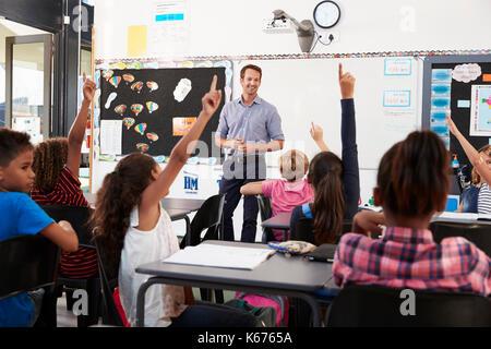 School kids raising hands in elementary school class - Stock Photo