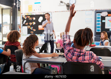 Teacher pointing to elementary school student in class - Stock Photo