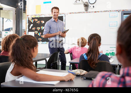 Teacher with tablet in front of elementary school class - Stock Photo