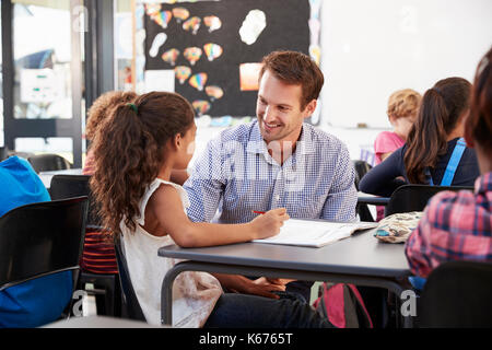 Teacher and schoolgirl at her desk, looking at each other - Stock Photo