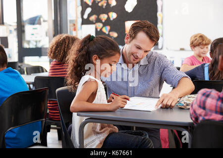 Teacher working with young schoolgirl at her desk in class - Stock Photo