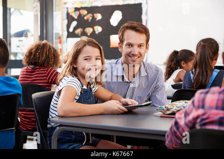 Teacher and schoolgirl using tablet in class look to camera - Stock Photo