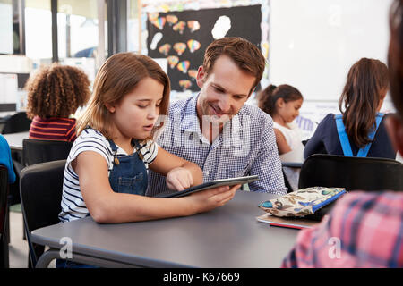 Teacher and young schoolgirl using tablet in classroom - Stock Photo