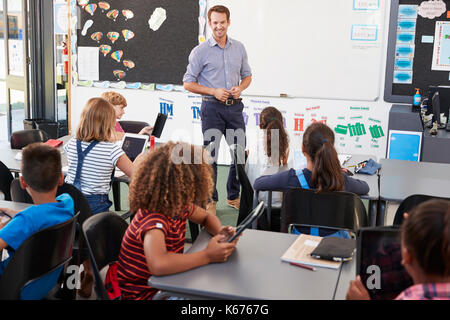Teacher standing in front of elementary school class - Stock Photo