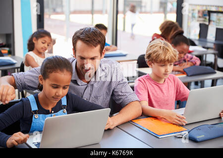 Teacher helping young students using laptops in class - Stock Photo