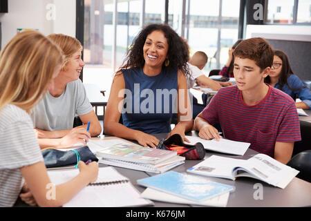 Teacher studying school books in class with high school kids - Stock Photo