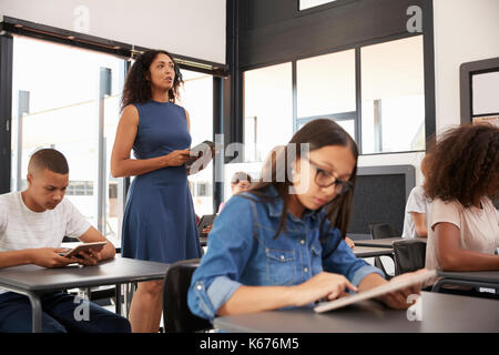 Teacher standing in the middle of her high school class - Stock Photo