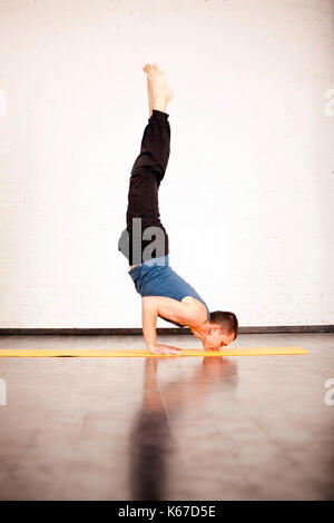 A young strong man doing yoga exercises - Salamba sirsasana, handstand with padmasana legs. - Stock Photo